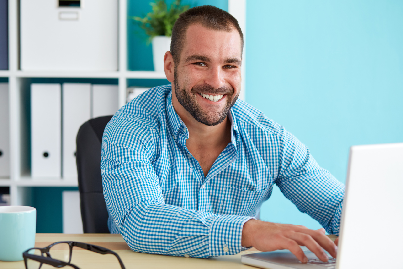Happy man working in modern office on computer
